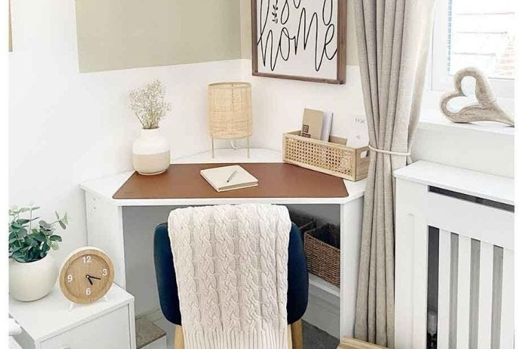 Bray corner office desk placed in the corner of a room with a grey office chair placed in front of it and a white knitted blanket placed over it. On the desk is a cream vase with dried flowers in and a notebook.