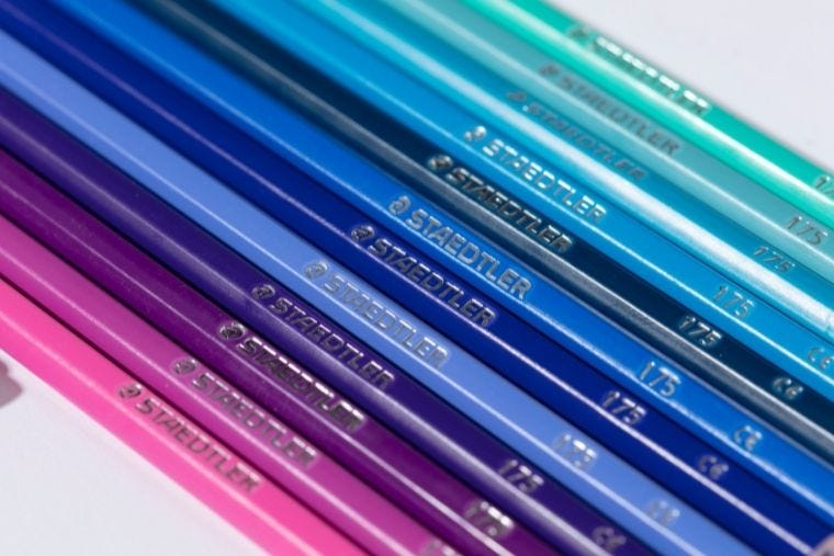 A selection of blue, purple and green shaded colouring pencils all arranged in a line next to each other.