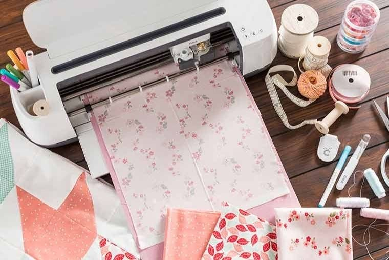 Cricut machine cutting a variety of fabrics including a floral pink square. The machine is on a dark brown table surrounded by ribbons.