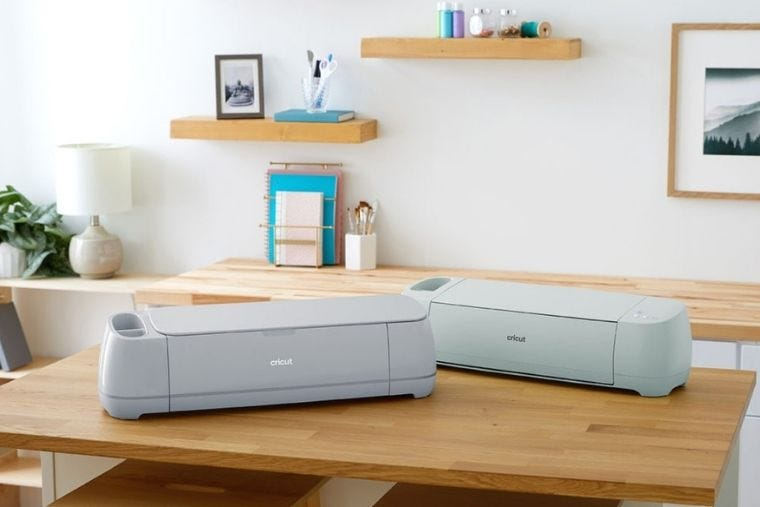 Two cricut machines sat on a kitchen table.