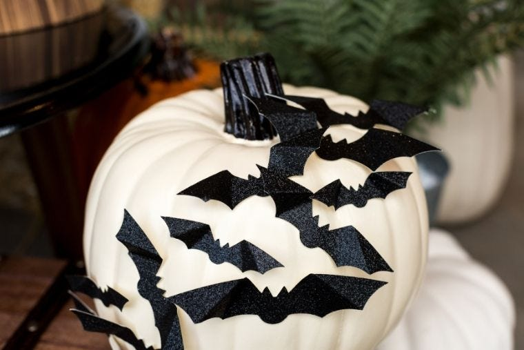 A white pumpkin is decorated with black paper bats made with a Cricut machine.
