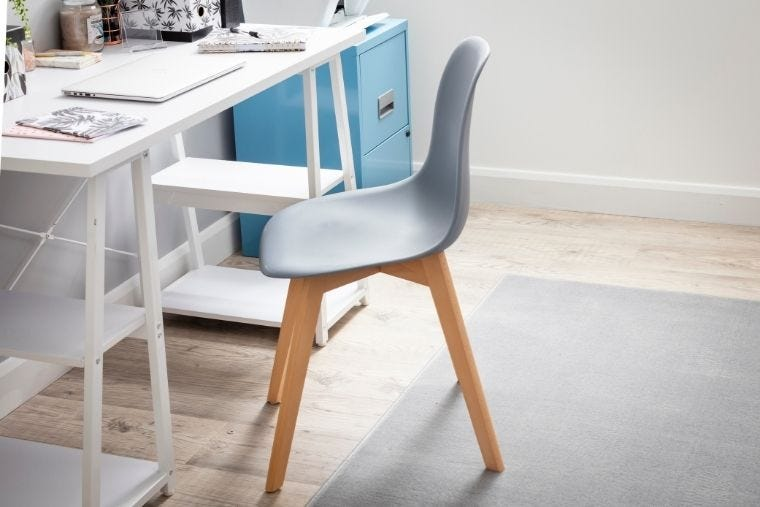 A grey desk chair in a neutral office space, it's sat in front of a white office desk that has a laptop and stationery sat on it.