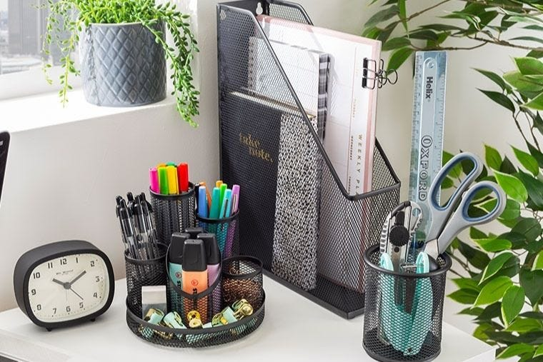 A white desk with an array of black mesh stationery storage placed on it. The storage contains different pens, pencils and notebooks.