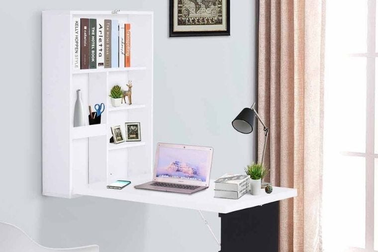 A white foldaway desk with a built in chalkboard and storage shelves. On it sits a laptop, desk lamp and books.