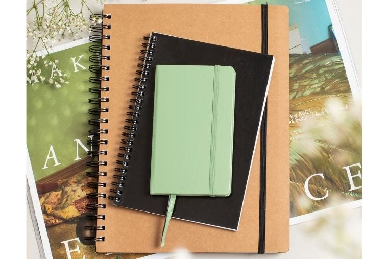 An A4 Kraft notebook is sat on top of an open magazine. On top of the A4 notebook are two smaller notebooks, sized A5 and A6.
