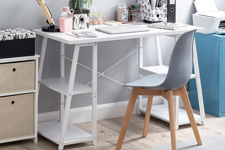 A small white home office desk with a grey chair placed in front of it. On the desk is an array of fashion stationery and storage.