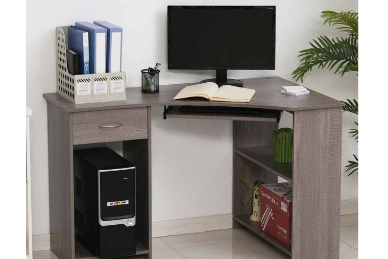 A brown corner desk with a desktop computer placed on it along with basic stationery storage.