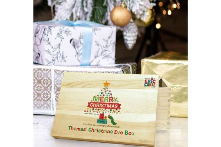 A personalised Hungry Caterpillar Christmas Eve box is sat underneath a Christmas tree.