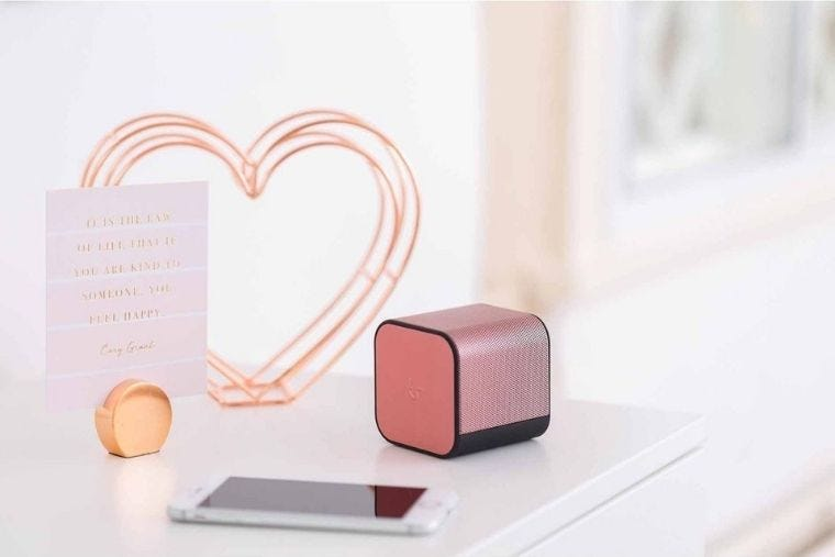 Rose gold KitSound BoomCube speaker sits on a white desk next to a mobile phone and rose gold wire heart desk decoration.