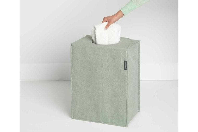 A light green laundry bag is placed on the floor while someone is placing laundry in it.