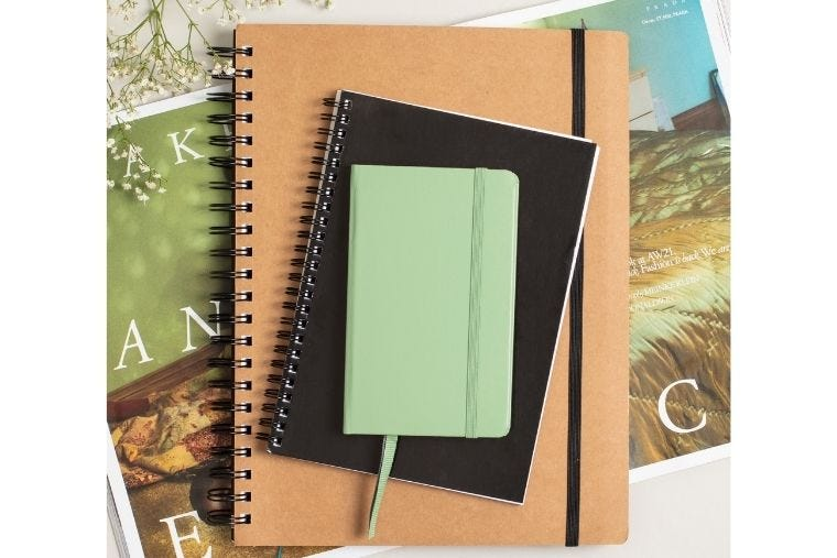 On top of an open magazine sits three different sized notebooks from A4 down to A6.
