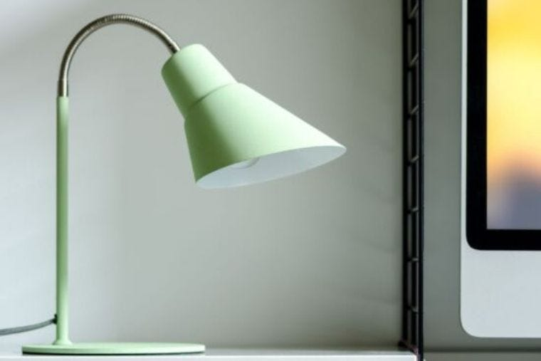 A Swedish green Wild and Wold Wild Wood Gooseneck desk lamp sits on a white