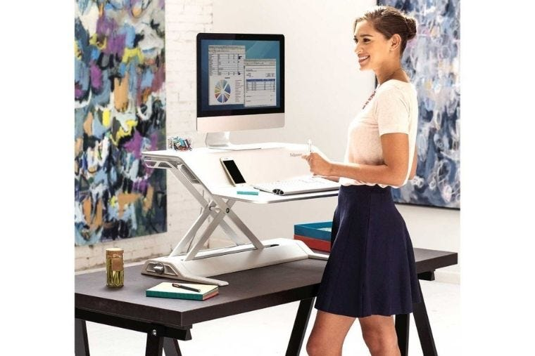 Standing workstation with a laptop placed on it and a woman standing in front of it.