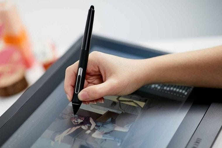 Wacom Cintiq 16 Graphics Display resting on a desk while a person draws using it.
