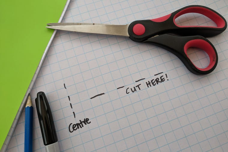 A flatlay photo demonstrating the first steps on how to sticky back plastic an exercise book. Displaying scissors, a pencil, pen and grid paper.